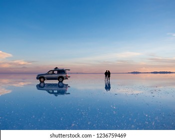 Exciting scenery of spacious Salar de Uyuni with couple and car reflection on mirror surface
