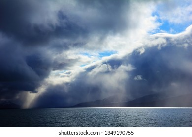 Exciting scenic view - dark water of Istfjorden under dramatic sky with bright sun shafts struck through the thunderstorm cloud near Barentsburg, Norway,  Svalbard, Spitsbergen island, Greenland sea