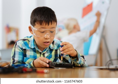 Exciting subject. Interested boy studying a new device while being at school