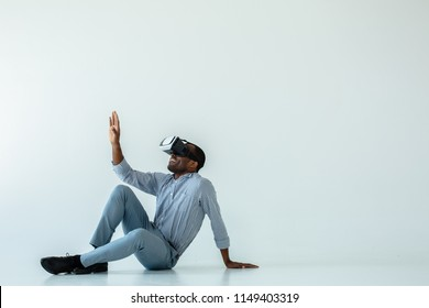 Exciting view. Cheerful afro american man sitting on the floor while testing vr glasses