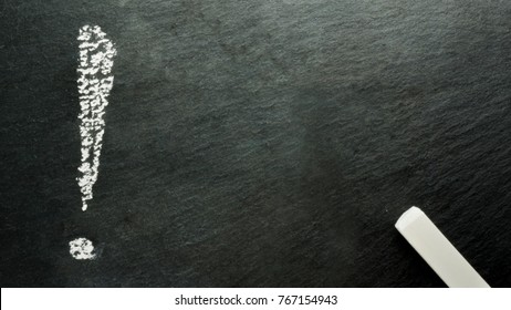 Exclamation mark written on black slate with white chalk