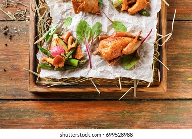 Excuisite restaurant food. Quails baked to golden crust with asparagus and chanterelles on grungy wooden platter on craft paper. Freshly cooked meals on rustic background with copy space, top view