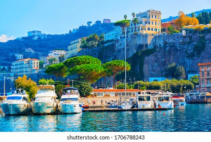 Excursion cruise boats and ships with tourists in luxury Marina Grande port in Sorrento near Naples on Tyrrhenian sea, Amalfi coast, Italy. Italian summer paradise. Mountains on Amalfitana coastline.