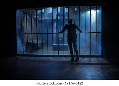 Execution concept. Death penalty guillotine miniature inside old prison. Old prison bars cell lock. Man inside jail. Horror view of Guillotine scale model in the dark