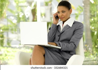 Executive Afro American woman using laptop on knees and giving a call will cell phone