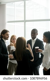 Executive business leaders team having discussion at coffee break in office, diverse businesspeople talking sharing ideas standing gathering together at meeting, training or conference, vertical view