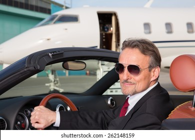 executive business man in a cabriolet in front of corporate private jet