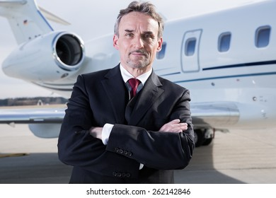executive business man in front of corporate jet