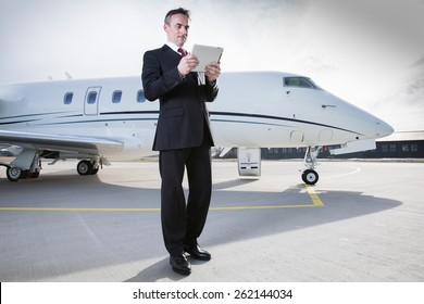 executive business man in front of corporate jet looking at tablet computer