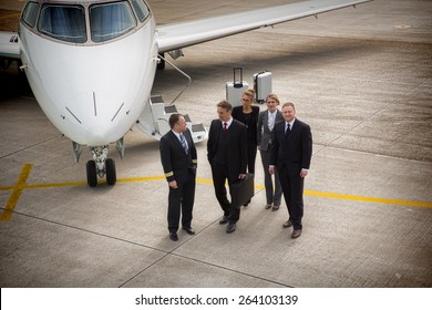 executive business team in front of corporate jet talking to pilot