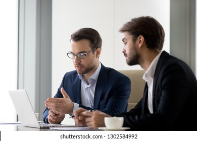 Executive businessmen colleagues working together helping in office teamwork on laptop discuss online project, financial advisor insurer salesman speaking consult client listen computer presentation
