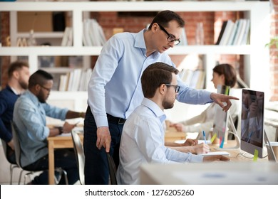 Executive corporate manager ceo helping male colleague with computer task in office, mentor talking supervising teaching training intern coworker explaining online work pointing on pc at workplace
