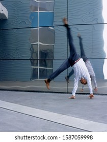Executive doing cartwheel in front of mirrored wall