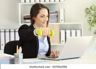 Executive exercising doing weights and working at office