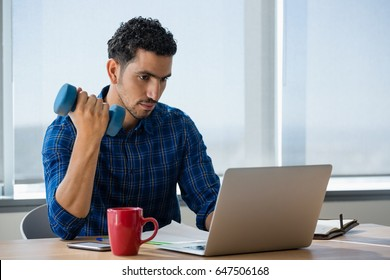 Executive exercising with dumbbells while using laptop in office