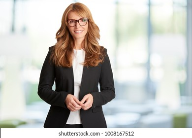 An executive financial businesswoman looking at camera and smiling while standing in the office after business meeting.