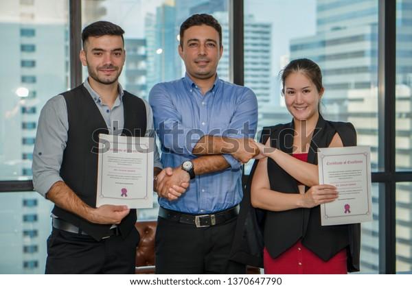 administración ejecutiva que otorga un certificado de excelencia a los ejecutivos caucásicos y asiáticos para recompensar su desempeño laboral