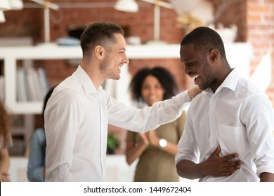 Executive manager businessman congratulating African American employee with job promotion, team leader touching subordinate shoulder, thanking for good work results at meeting, showing respect