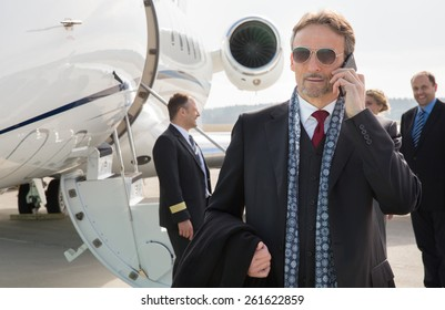 executive manager in front of corporate jet using a smart phone