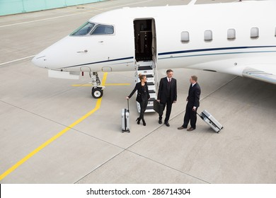 executive manager in front of corporate jet