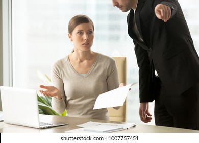 Executive manager giving written dismiss order to shocked female employee, pointing at door and asking her to leave workplace immediately, frustrated woman receiving unexpected dismissal notification