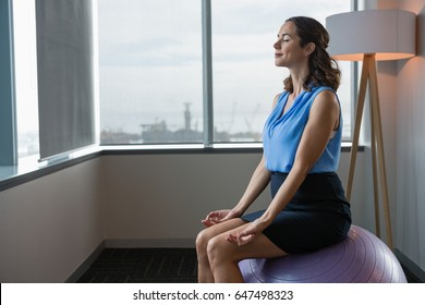 Executive meditating on fitness ball in office