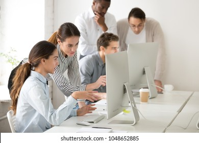 Executive mentor explaining intern or new employee online task pointing at computer screen, female boss supervisor teaching young girl to use corporate software or helping with difficult assignment