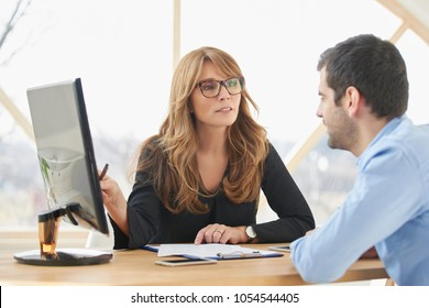 Executive middle aged businesswoman sitting at desk in front of laptop and doing some paperwork while giving sales advice to her young assistant. Brainstorming at the office.