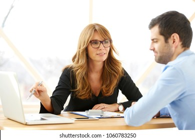 Executive middle aged investment advisor businesswoman sitting in front of laptop with young financial assistant businessman and consulting about a new project. Brainstorming at the office.