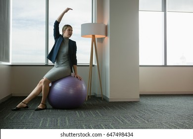 Executive performing stretching exercise on fitness ball in office
