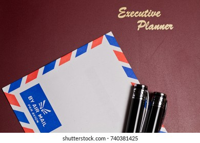 executive planner with white by air mail envelopw and pens  in landscape orientation