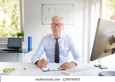 Executive senior businessman doing some paperwork while sitting at office desk in front of computer.