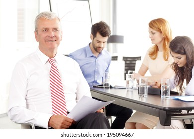 Executive senior businessman smiling at meeting. Background with colleagues.