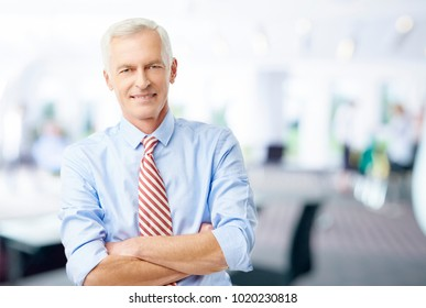 An executive senior financial advisor businessman standing with arms crossed at the office and looking at camera.