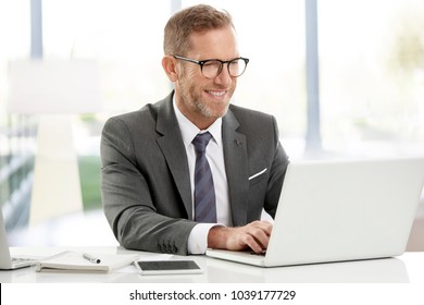 Executive senior financial director businessman doing some paperwork while sitting at desk and working on laptops.