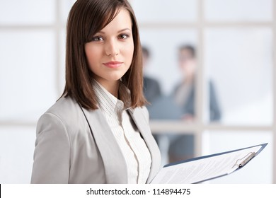 Executive with tablet on the glass wall background with people