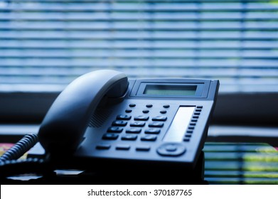 Executive VoIP desk phone with traditional corded headset and the business office window blinds in the background. Shallow depth of field - focus on the center of the phone