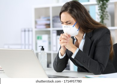 Executive woman wearing protective mask praying with eyes closed on a desk at the office