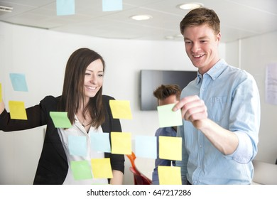 Executives Discussing Over Notes Stuck On Glass In Office