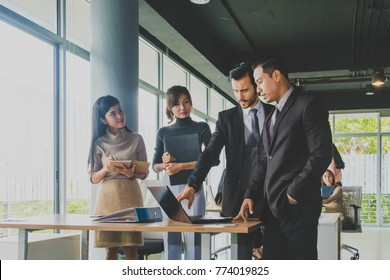 Executives and secretaries are discussing about the job information in a computer notebook.