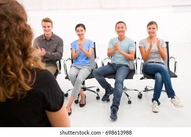 Executives sitting in seminar applauding