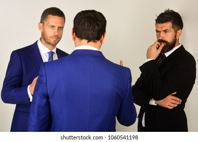 Executives trying to find compromise on light grey background. Men with beard and thoughtful faces discuss business. Businessmen wear smart suits and ties. Business and compromise concept.