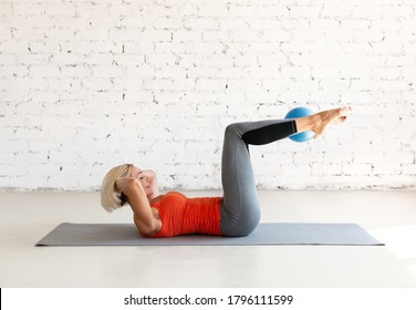 Exercise for abs with small fit ball. Fit caucasian woman practice pilates lying on the mat in loft white studio indoor, selective focus. Workout, fitness, trainer, coach, healthy lifestyle concept.
