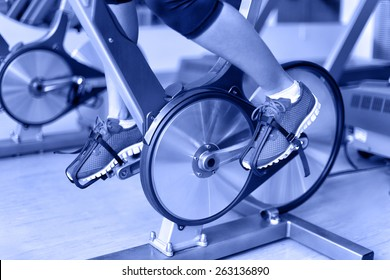 Exercise bike with spinning wheels. Woman excising biking in fitness center. closeup of pedals. Professional fitness center equipment.