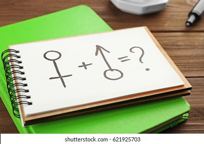 Exercise book with male and female symbols on wooden background