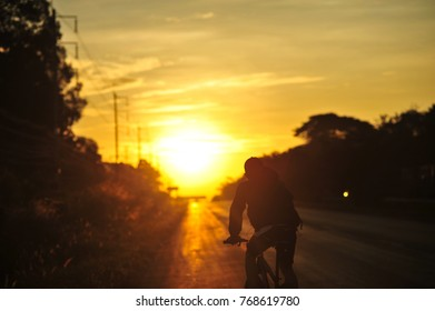 Exercise by bicycle in morning road between sunrise