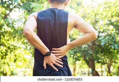 Exercise decrease back pain, close up young sports man holding back in the outdoor