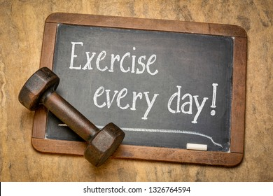 exercise every day - white chalk text on a slate blackboard with a dumbbell