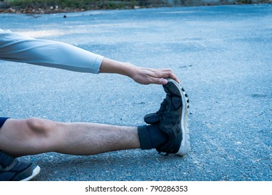 Exercise fitness training concept : Healthy young man warming up at the park outdoor. She is stretching arms and leg.