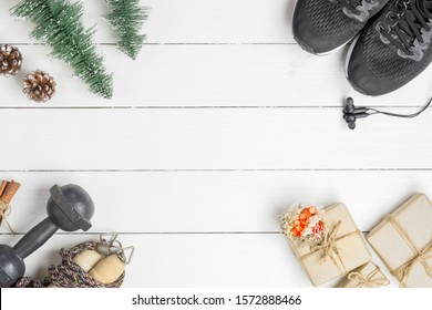 Exercise, Fitness,  and Working Out Merry Christmas and Happy new year Festive healthy lifestyle background concept. Dumbbells, sports shoes, Jump ropes, gift box and Christmas ornaments on white wood